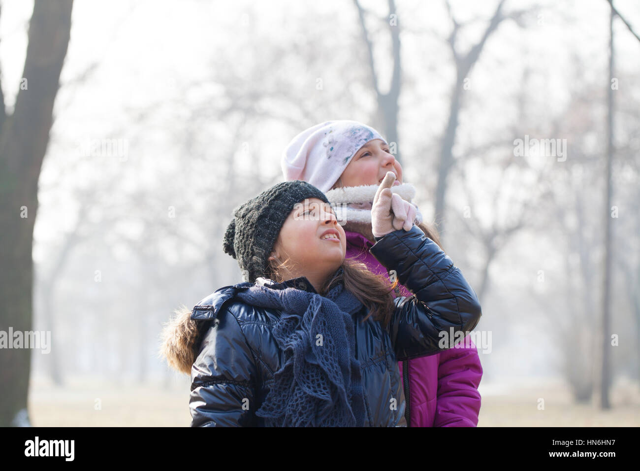 Two little girls with caps and scarves play, selective focus and small depth of field - Stock Image