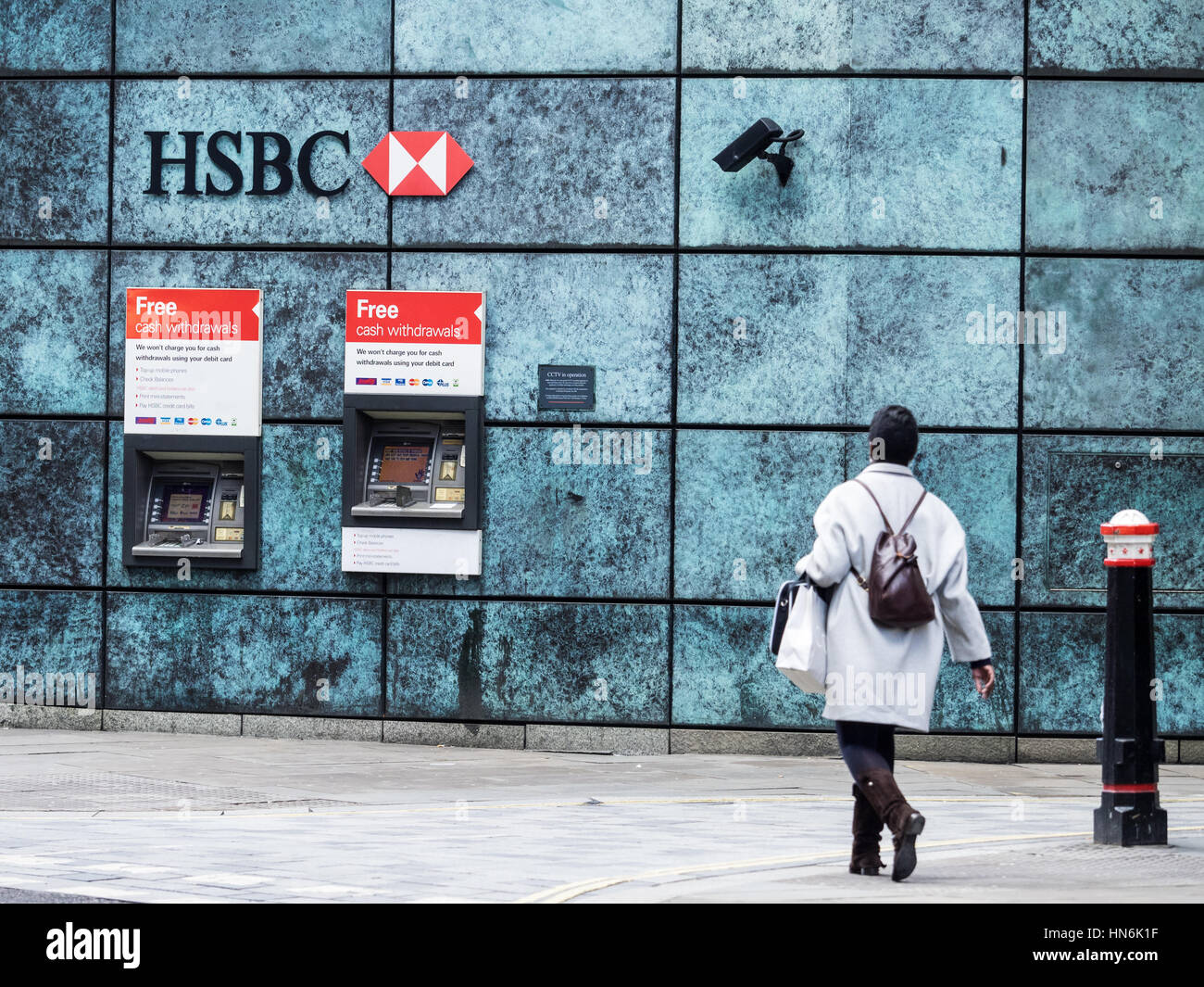 A woman walks towards HSBC cash machines in Central London Stock Photo