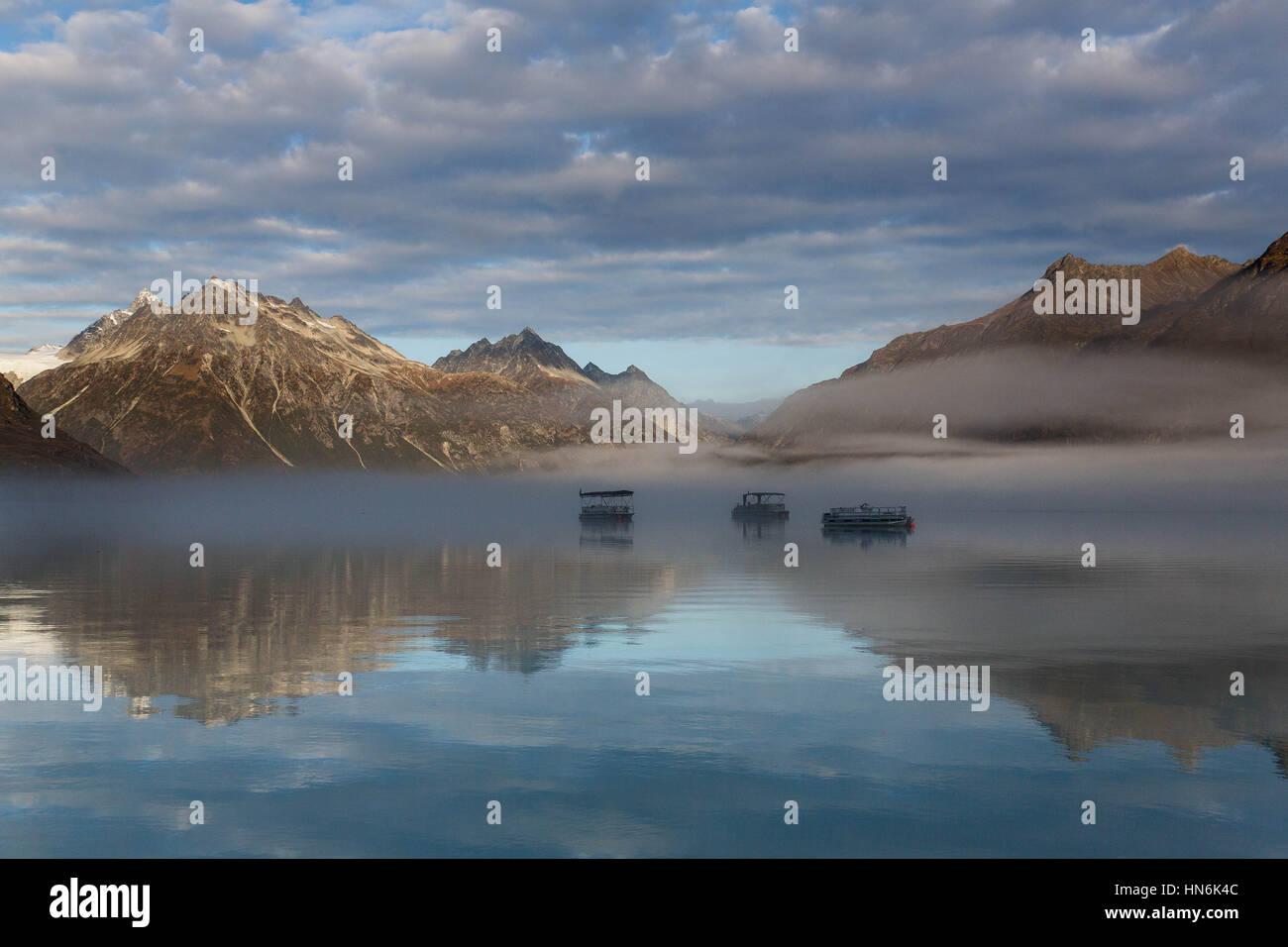 Three boats on a calm morning on Crescent Lake near Mount Redoubt, Lake Clark National Park, Alaska, USA - Stock Image
