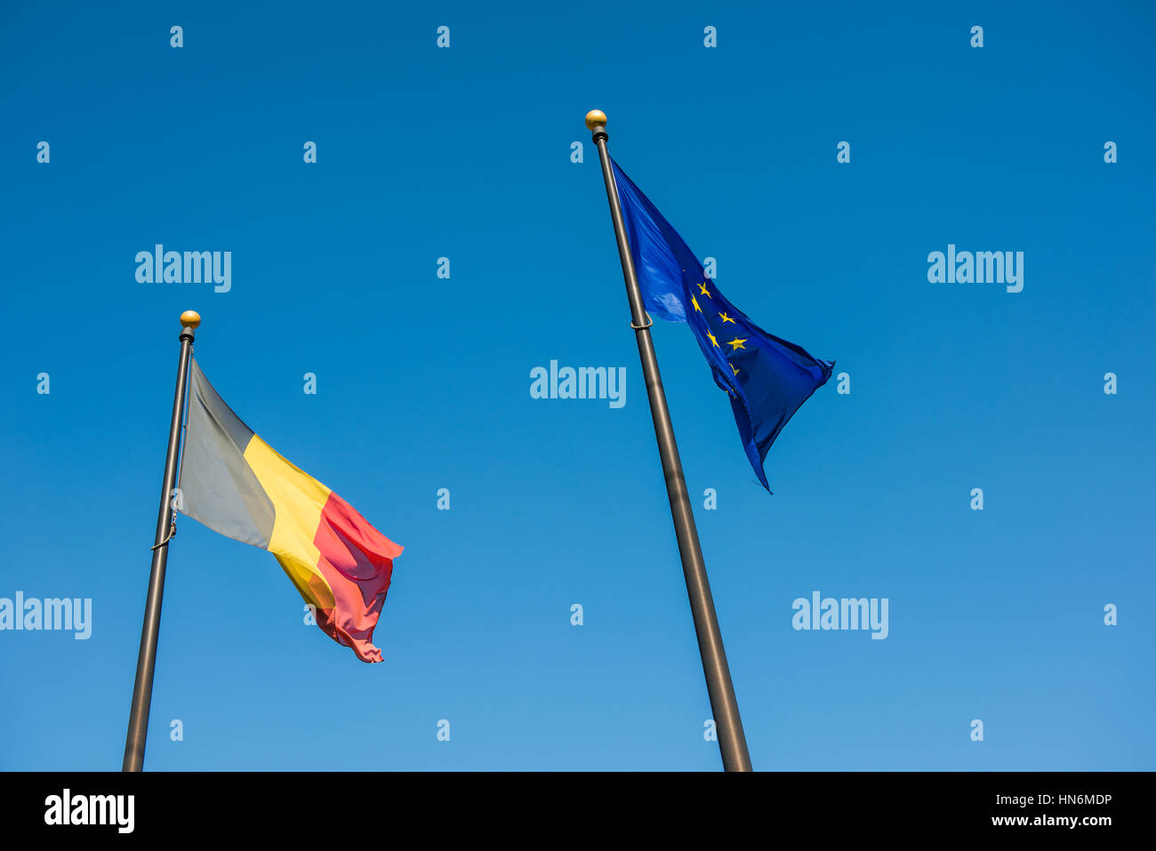 Belgian and European Union flags against blue sky - Stock Image
