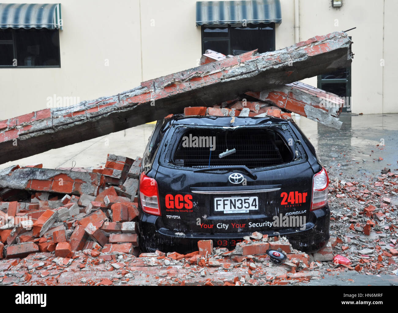Christchurch, New Zealand - March 2011: A car is crushed by a collapsed brick wall on March 20, 2011 in Christchurch - Stock Image