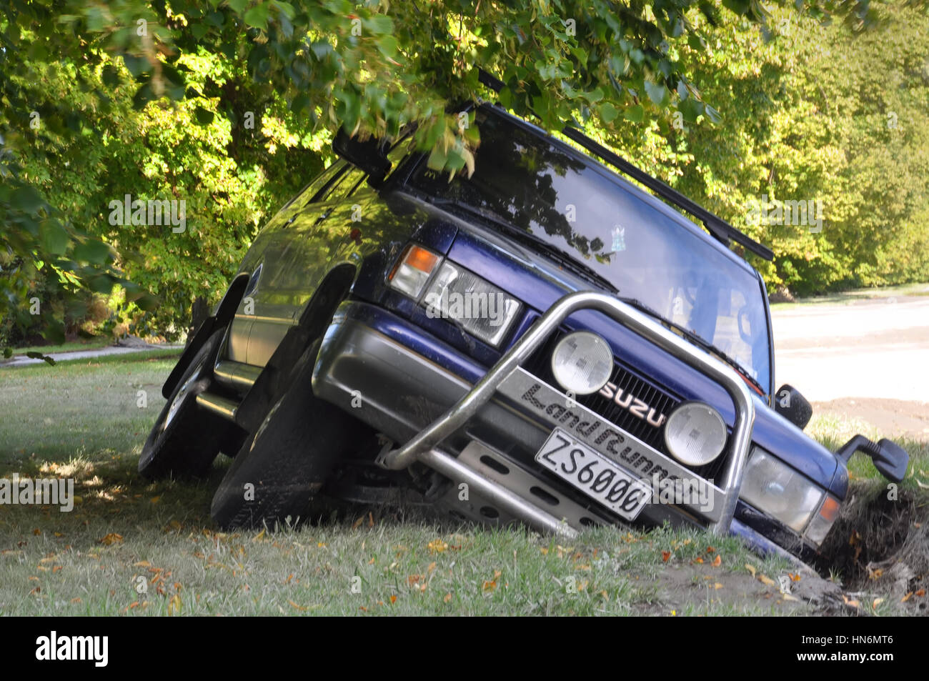 4WD Car falls into a giant crack left in the side of the road by a massive Eathquake in Christchurch, New Zealand. - Stock Image