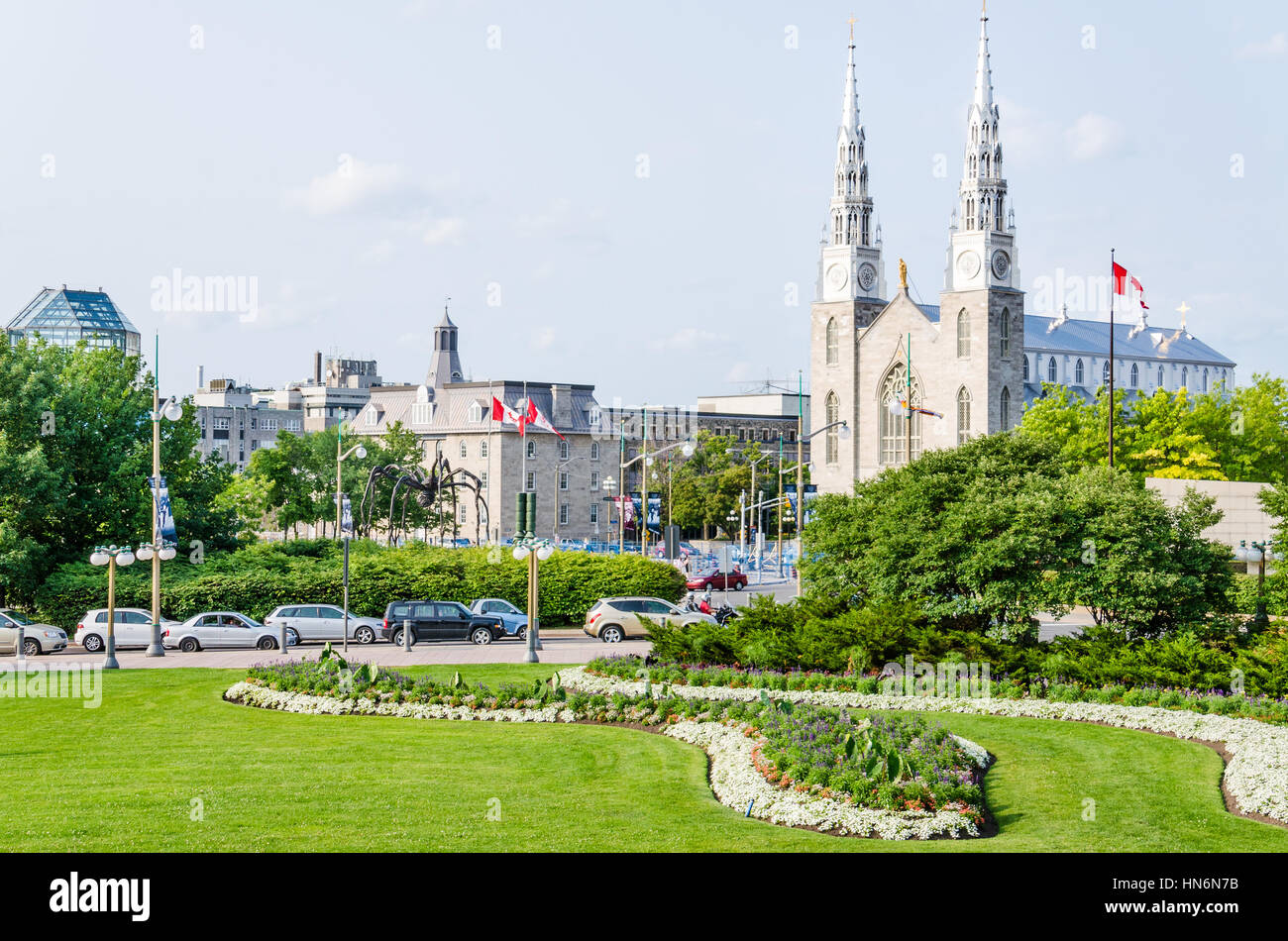 Ottawa, Canada - July 24, 2014: Notre-Dame Cathedral roman catholic Basilica with green trees and park with flags - Stock Image