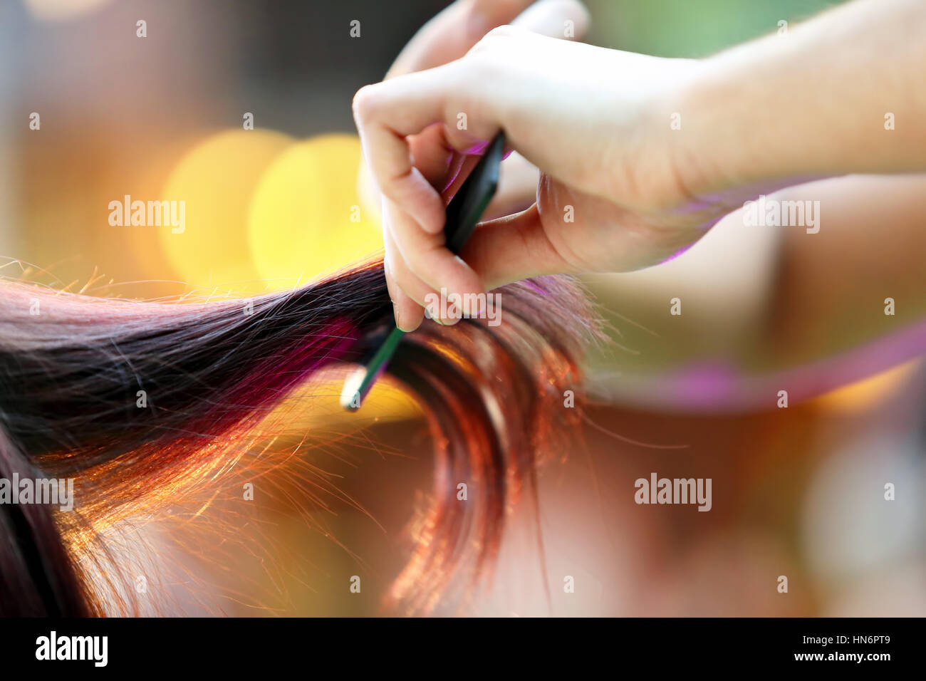 Hairdresser cutting and modeling brown hair by scissors and comb - Stock Image