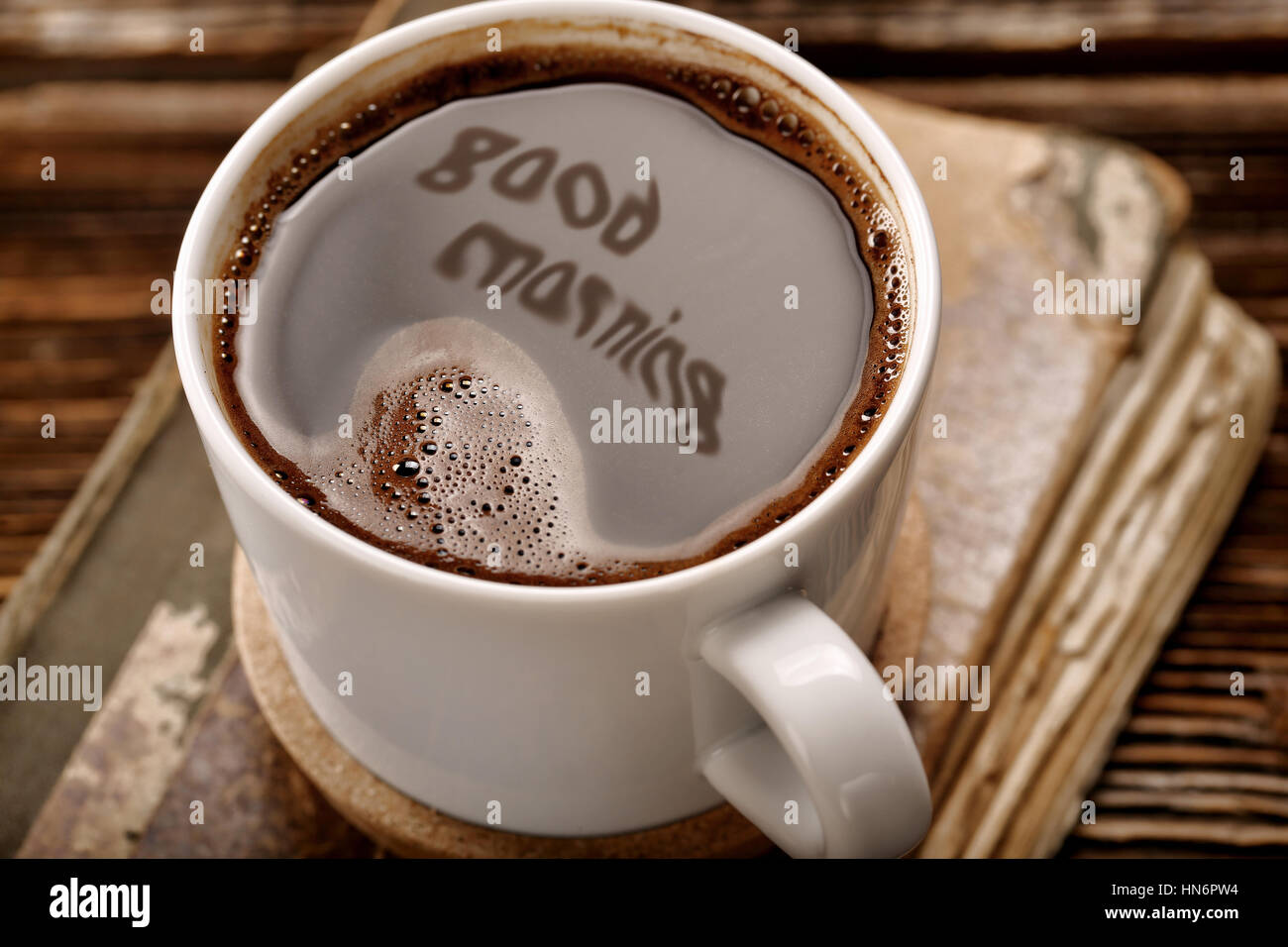Cup of coffee and old book on wooden background with good morning inscription - Stock Image