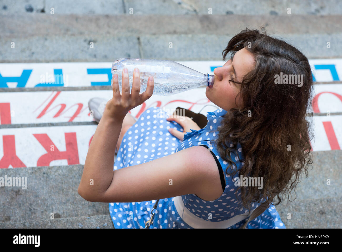 Young woman with blue polka dot dress sitting on steps drinking carbonated water in a clear bottle - Stock Image