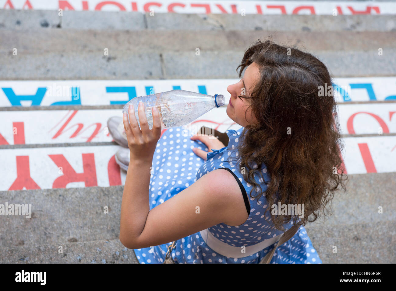 Young woman with blue polka dot dress sitting on steps drinking carbonated water in a clear bottle and laughing - Stock Image