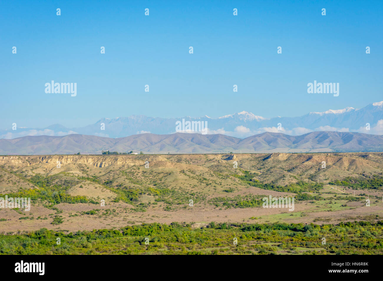 River, green meadow, golden fields and mountains with snow peaks, amazing landscapes of Azerbaijan - Stock Image