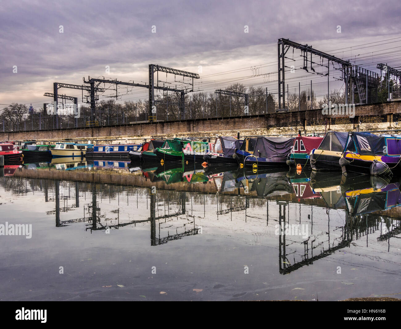 Canal boats moored on Regent's Canal with Train lines into St Pancras Station in background, London, UK. - Stock Image