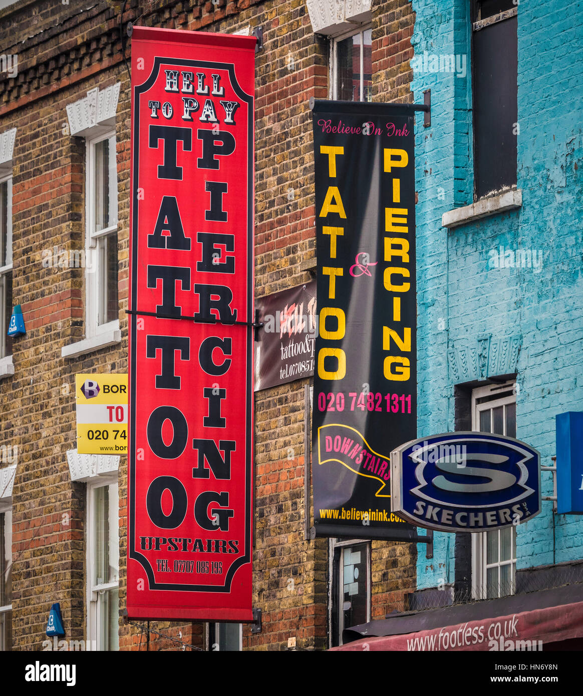 tattoo and Piercing advertising signs on outside of buildings, Camden, London, UK. - Stock Image