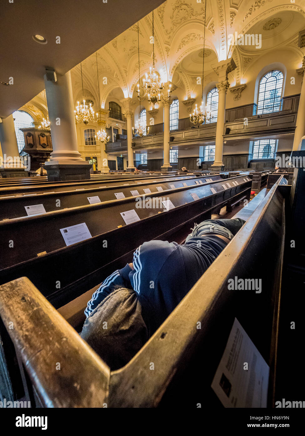 Homeless person sleeping in pews of St Martin-in-the-Fields, English Anglican church at the north-east corner of Stock Photo