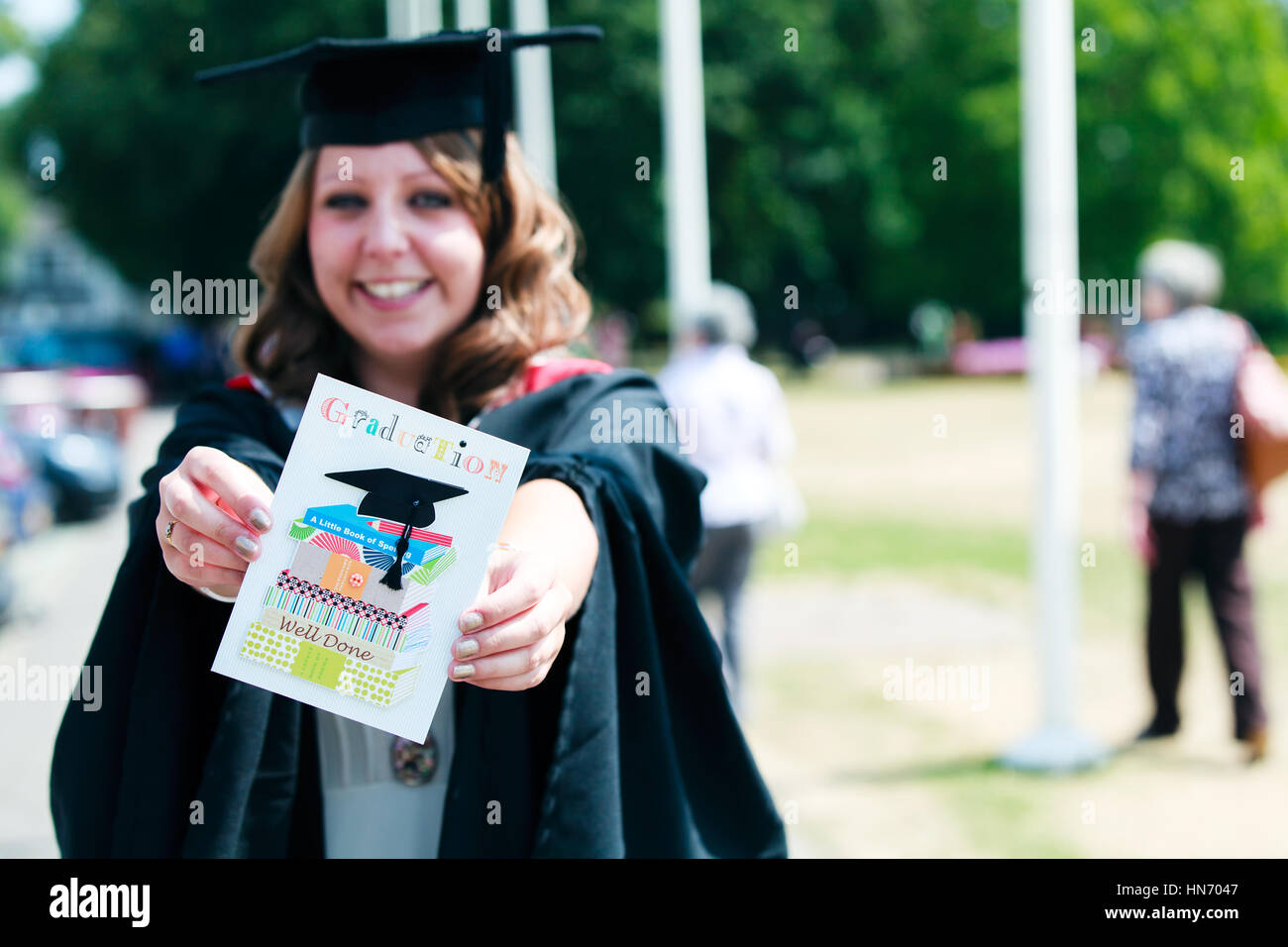 A university graduate, wearing a mortarboard and gown holds up a ...