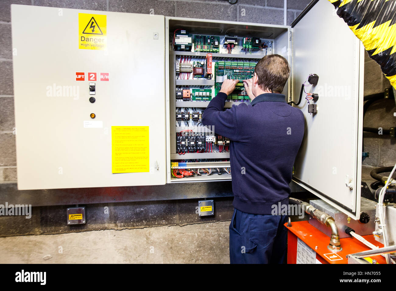 An electrician working on an electronic control panel situated in a control box - Stock Image