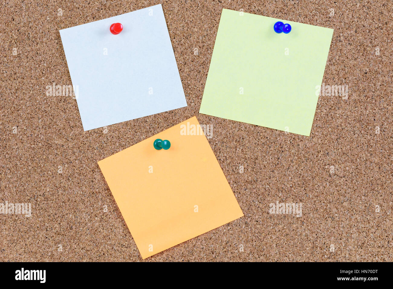 Various sticky notes on an office cork bulletin board. - Stock Image