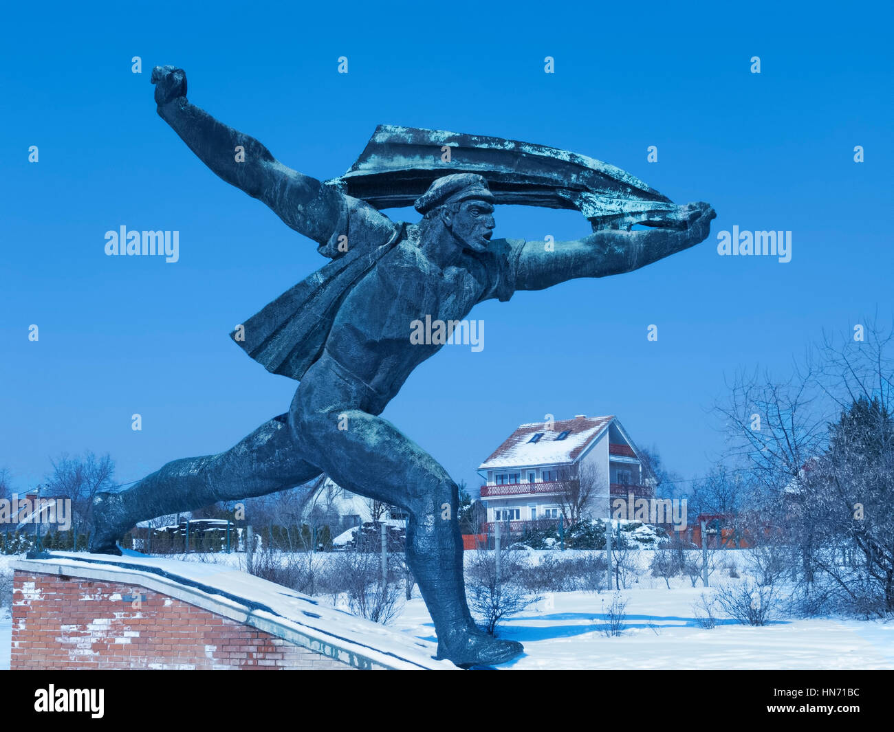 The memorial to the  Hungarian Socialist Republic, one of the statues in a Snow covered Memento Park, Budapest.. - Stock Image