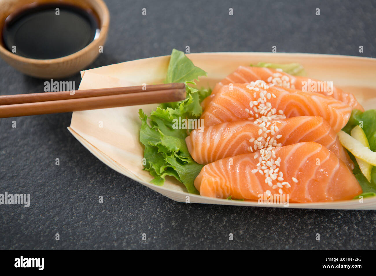 Sushi on boat shaped plate with chopsticks and sauce - Stock Image