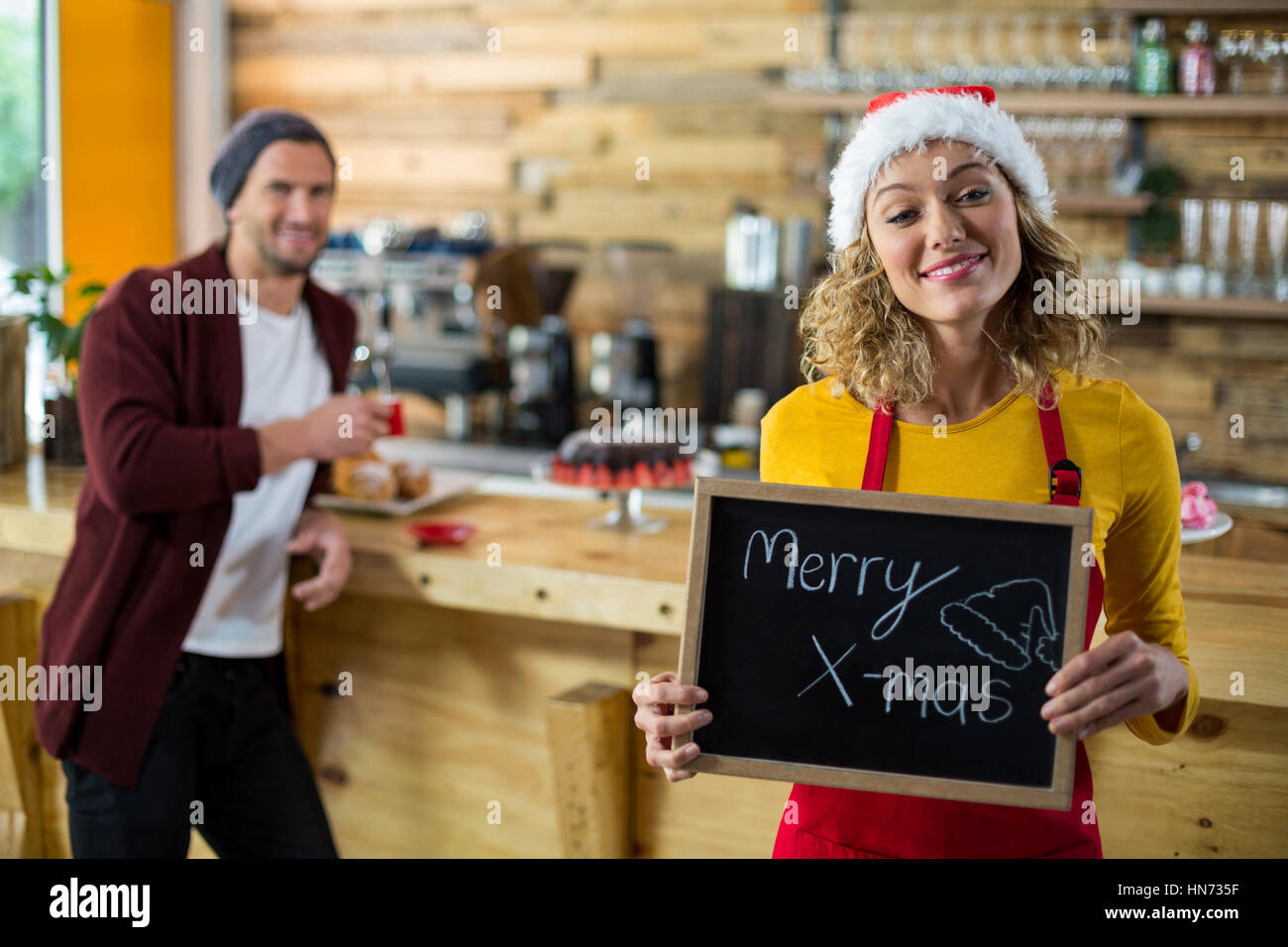 Portrait of smiling waitress standing with merry x mas sign board in cafe - Stock Image