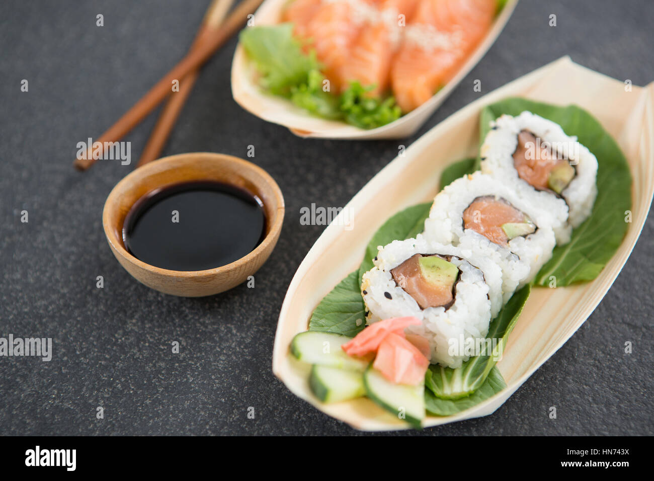 Sushi on boat shaped plate with chopsticks and sauce Stock Photo