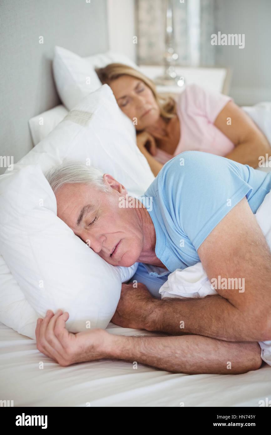 Senior couple sleeping on bed in bedroom - Stock Image