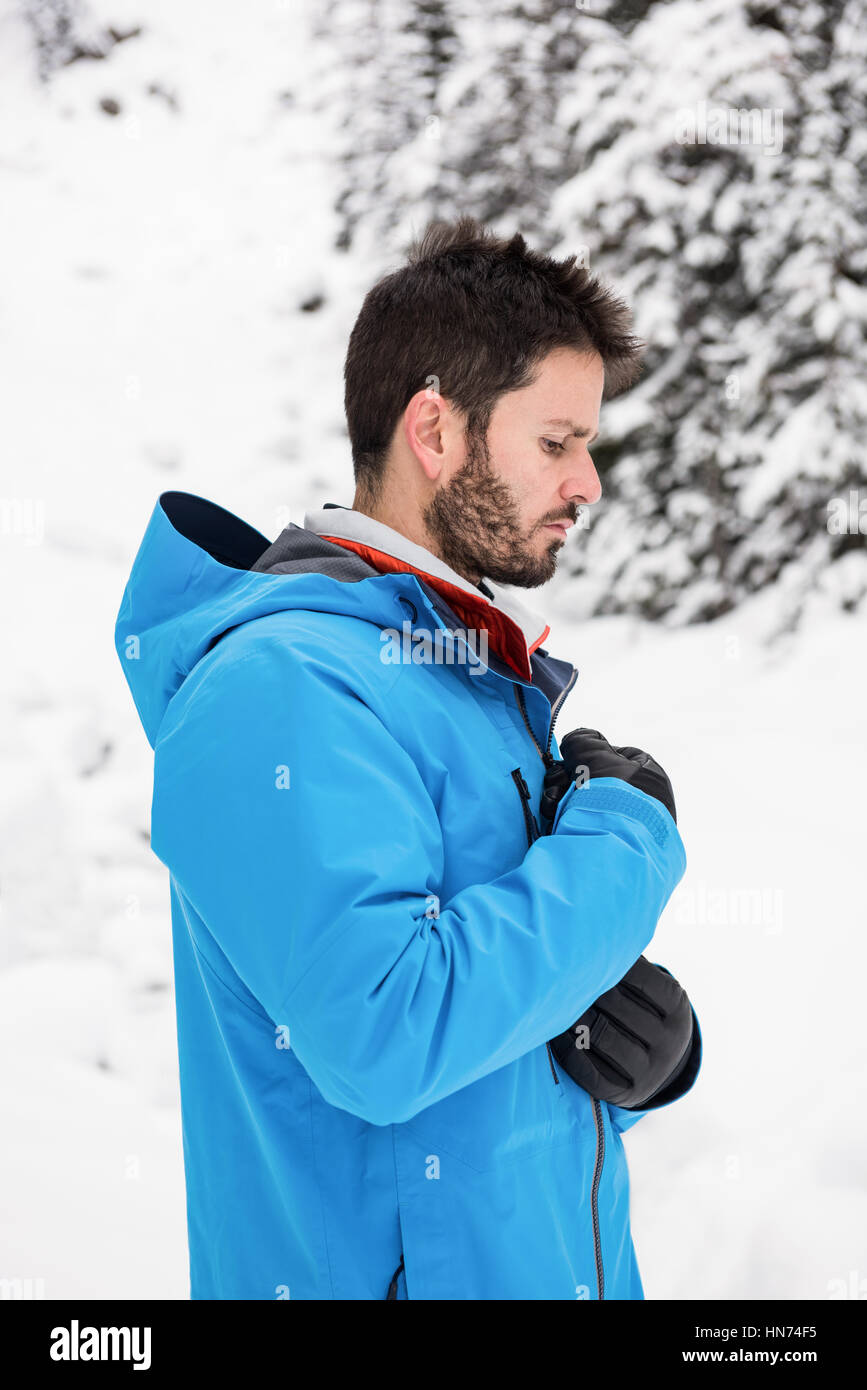 Side view of skier zipping his jacket on snowy mountains - Stock Image