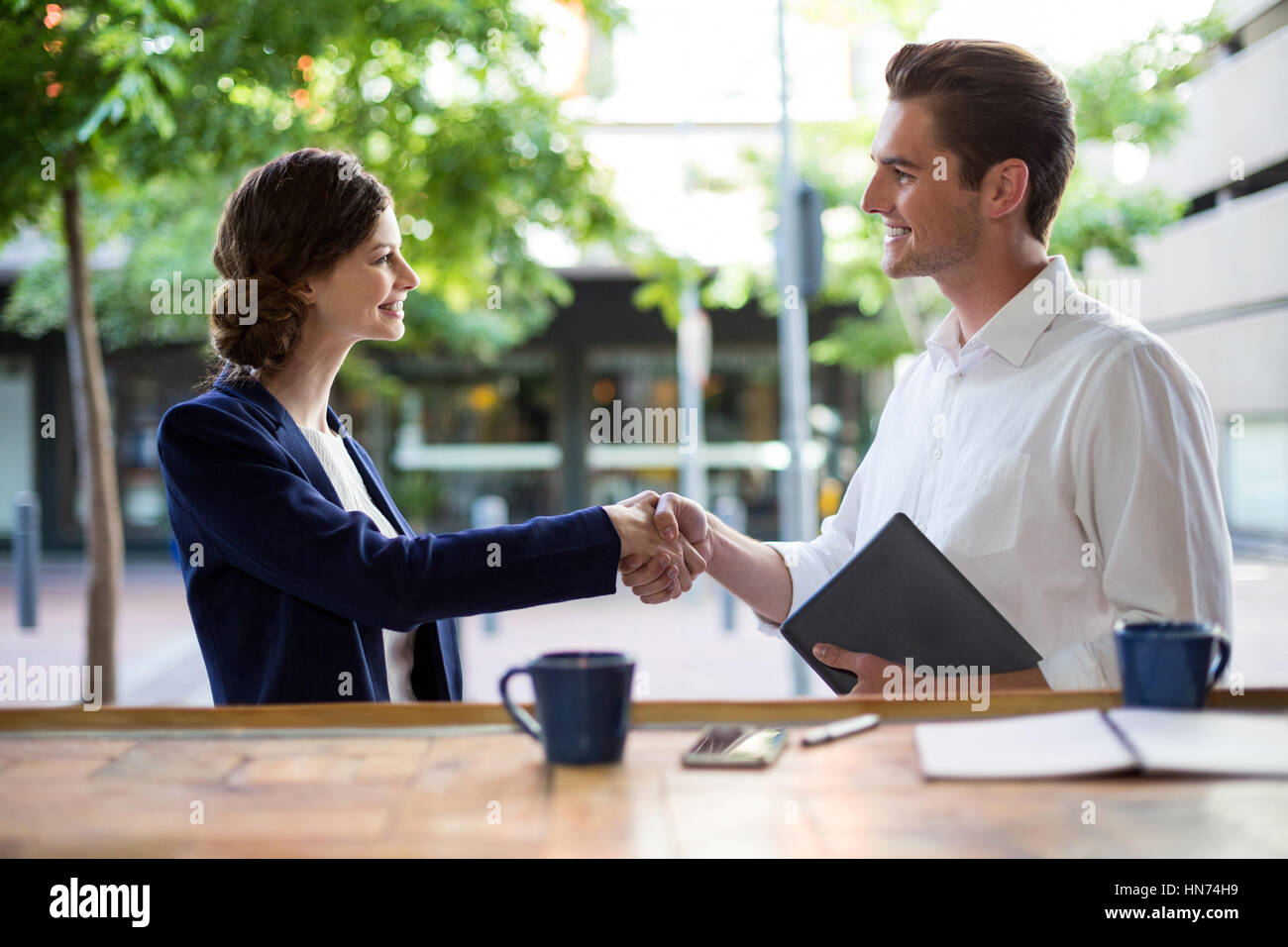 Businesswoman shaking hands with businessman at counter in cafe - Stock Image