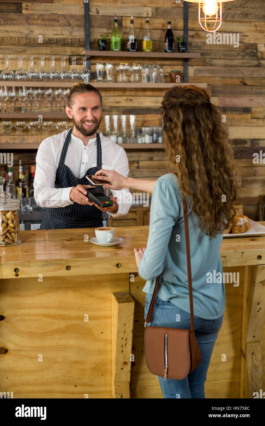 Woman paying bill through smartphone using NFC technology in cafe Stock Photo