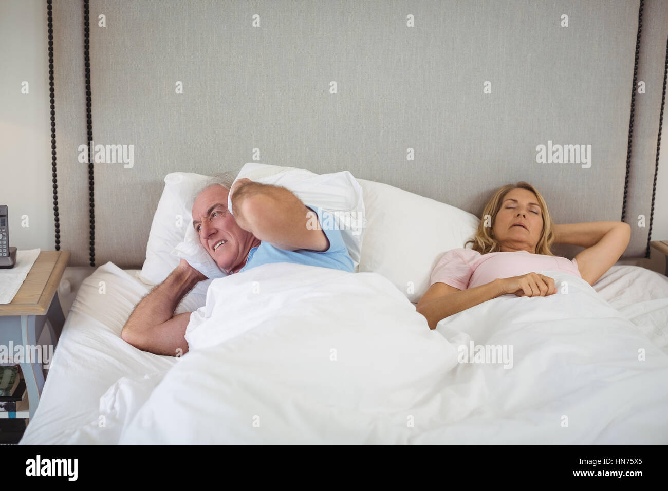 Senior man lying on bed and covering his ears with pillow in bedroom - Stock Image