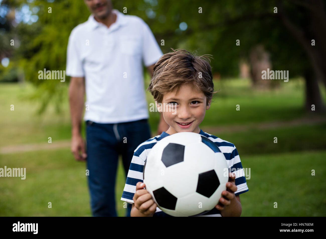 Father and son playing football in park Stock Photo