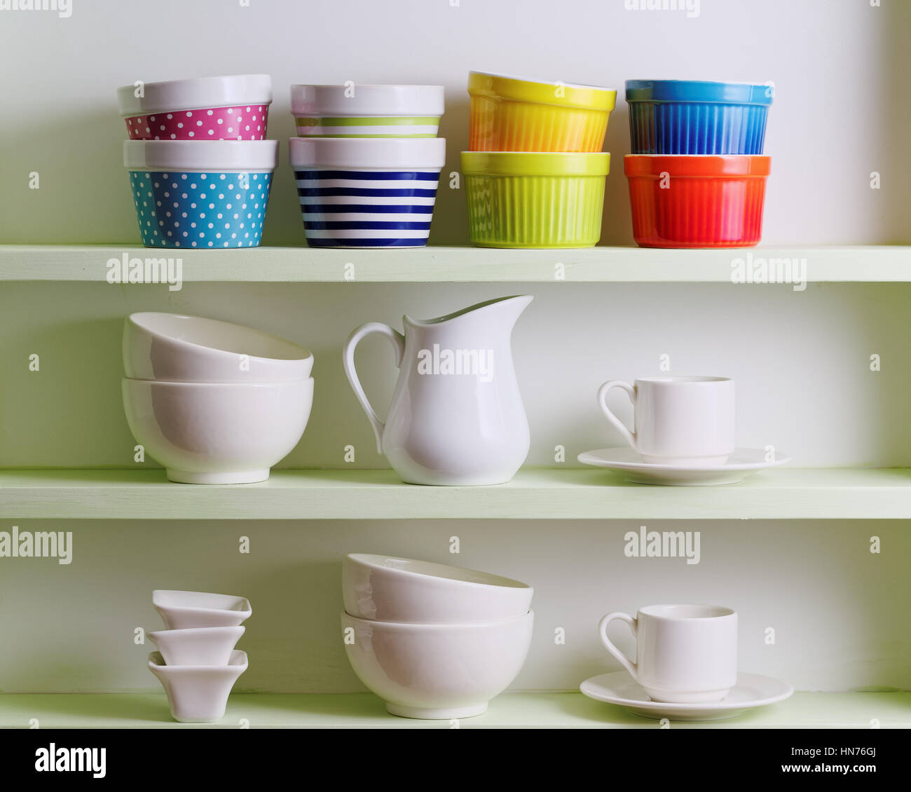 Variety of ceramics on shelf. Colorful bowls, cups and white dishware. - Stock Image