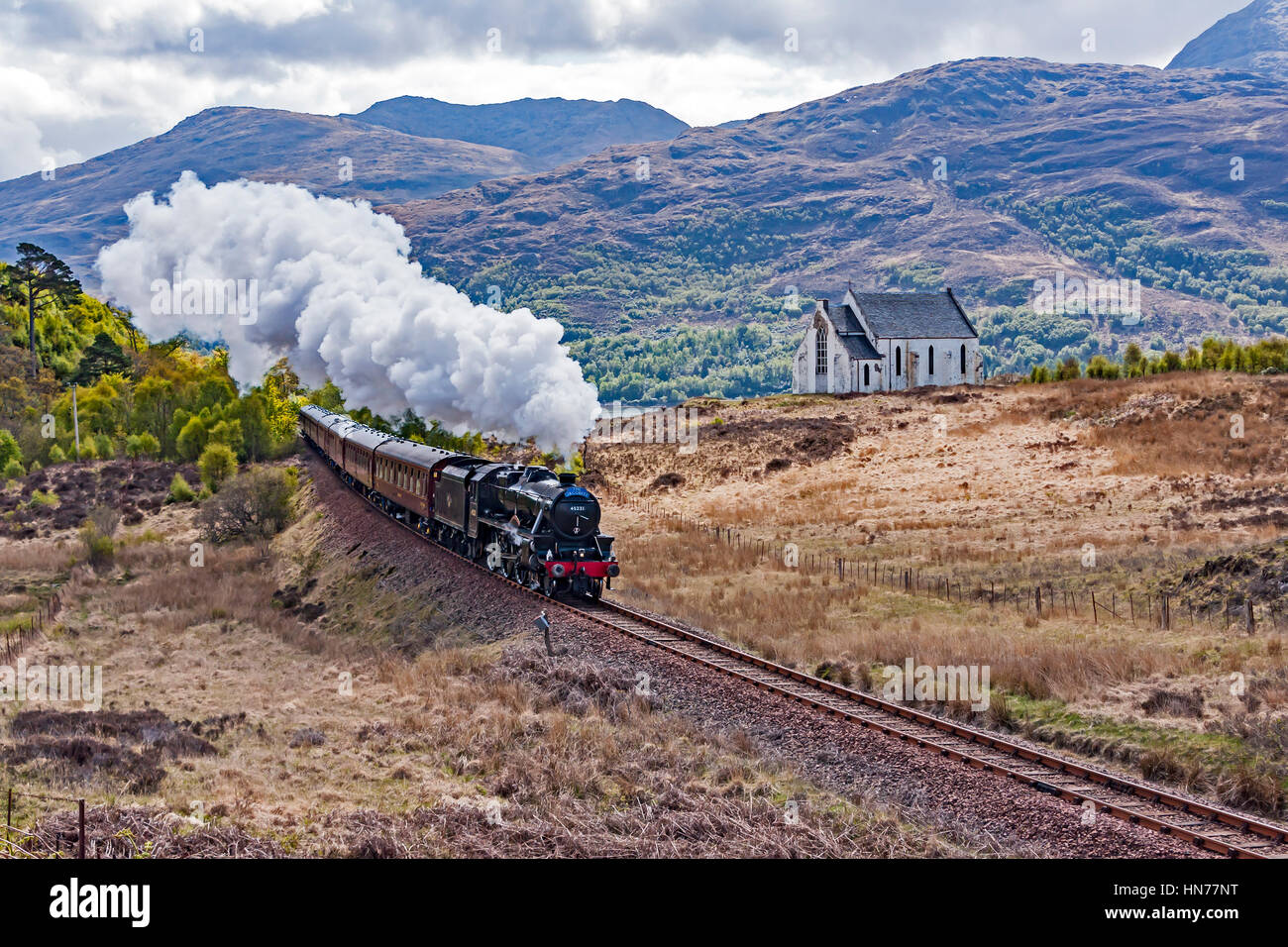 Stanier Class 5 4-6-0 No. 45231 steam engine powers The Jacobite past the church at Polnish West Highlands of Scotland - Stock Image