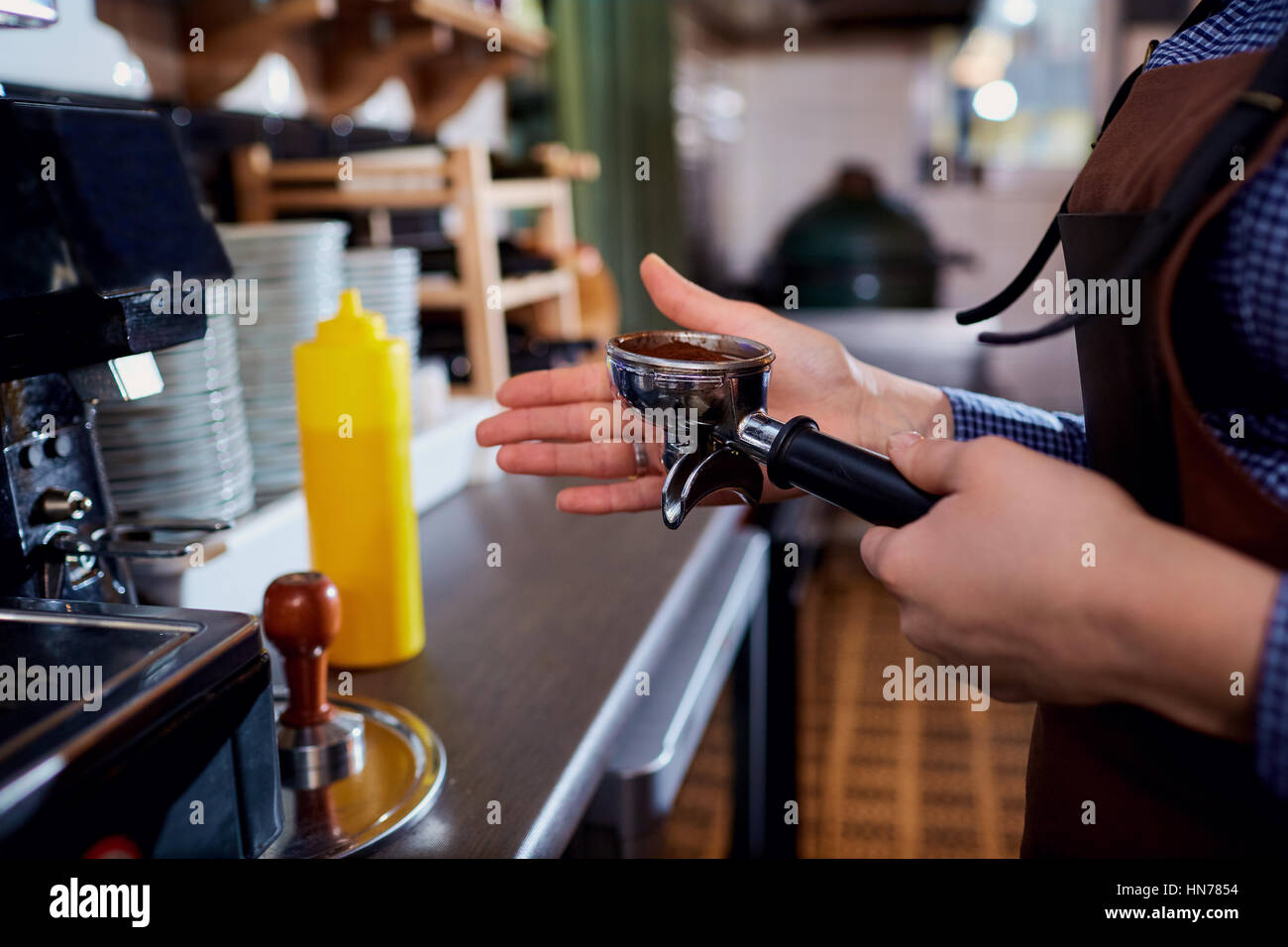 Hands baristas make  at the cappuccino machine in the bar - Stock Image