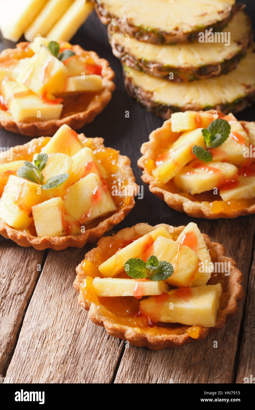 Tart filled with fresh pineapple and jam closeup on the table. vertical - Stock Image