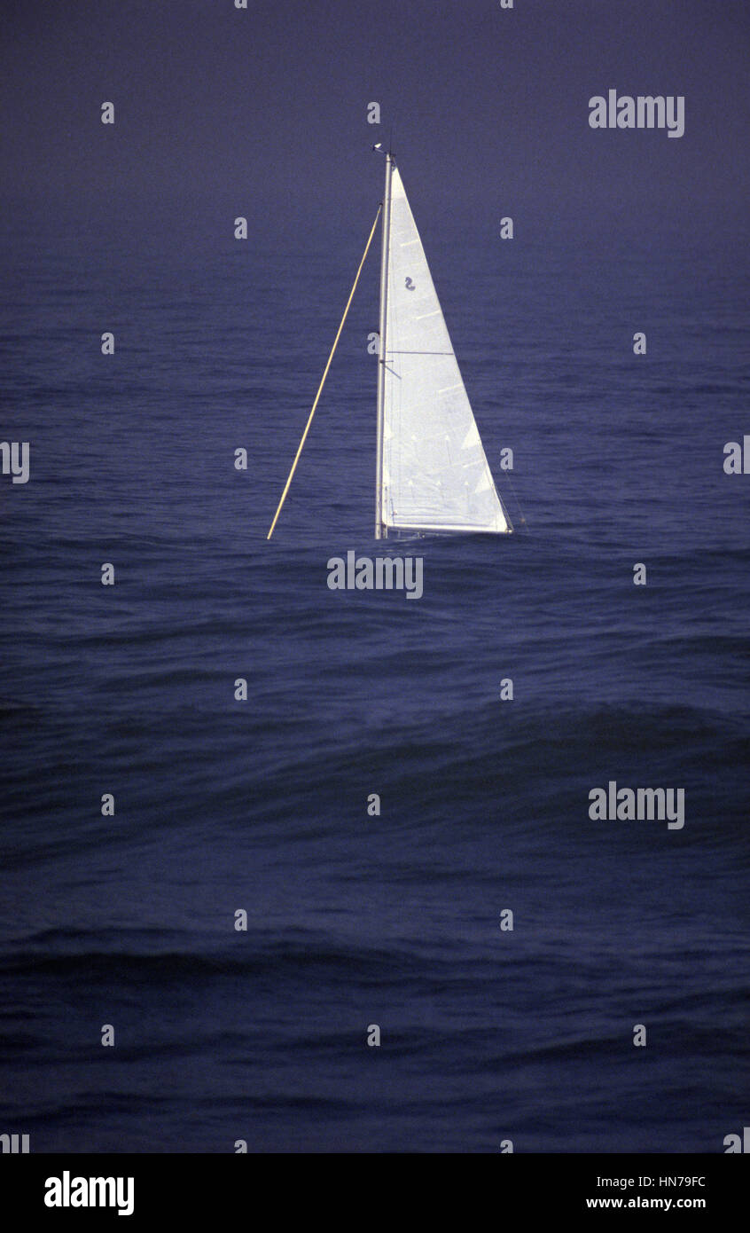 A sailboat flounders between the swells with only the sail visible above the swell on a windless sea. - Stock Image