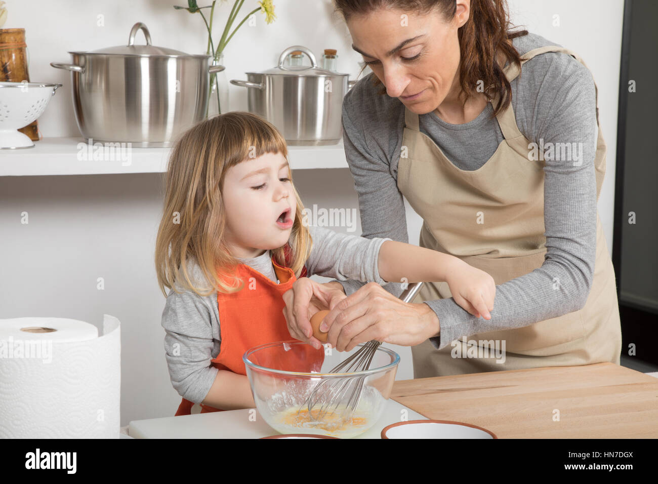 three years old child and woman mother with beige apron, in teamwork, cooking a sponge cake at kitchen home- Angry - Stock Image