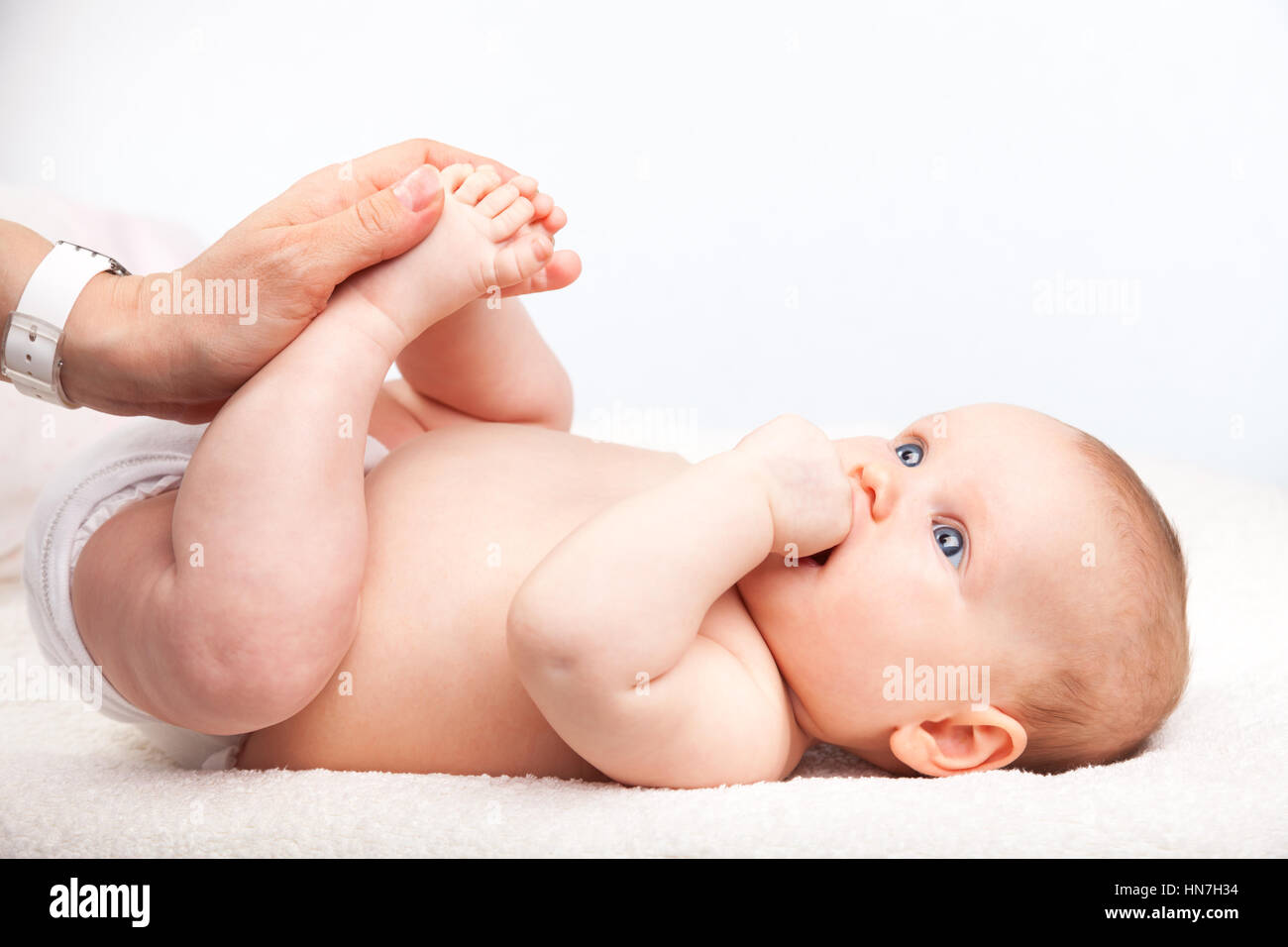 Close-up shot of three month baby girl receiving leg massage from a female massage therapist - Stock Image