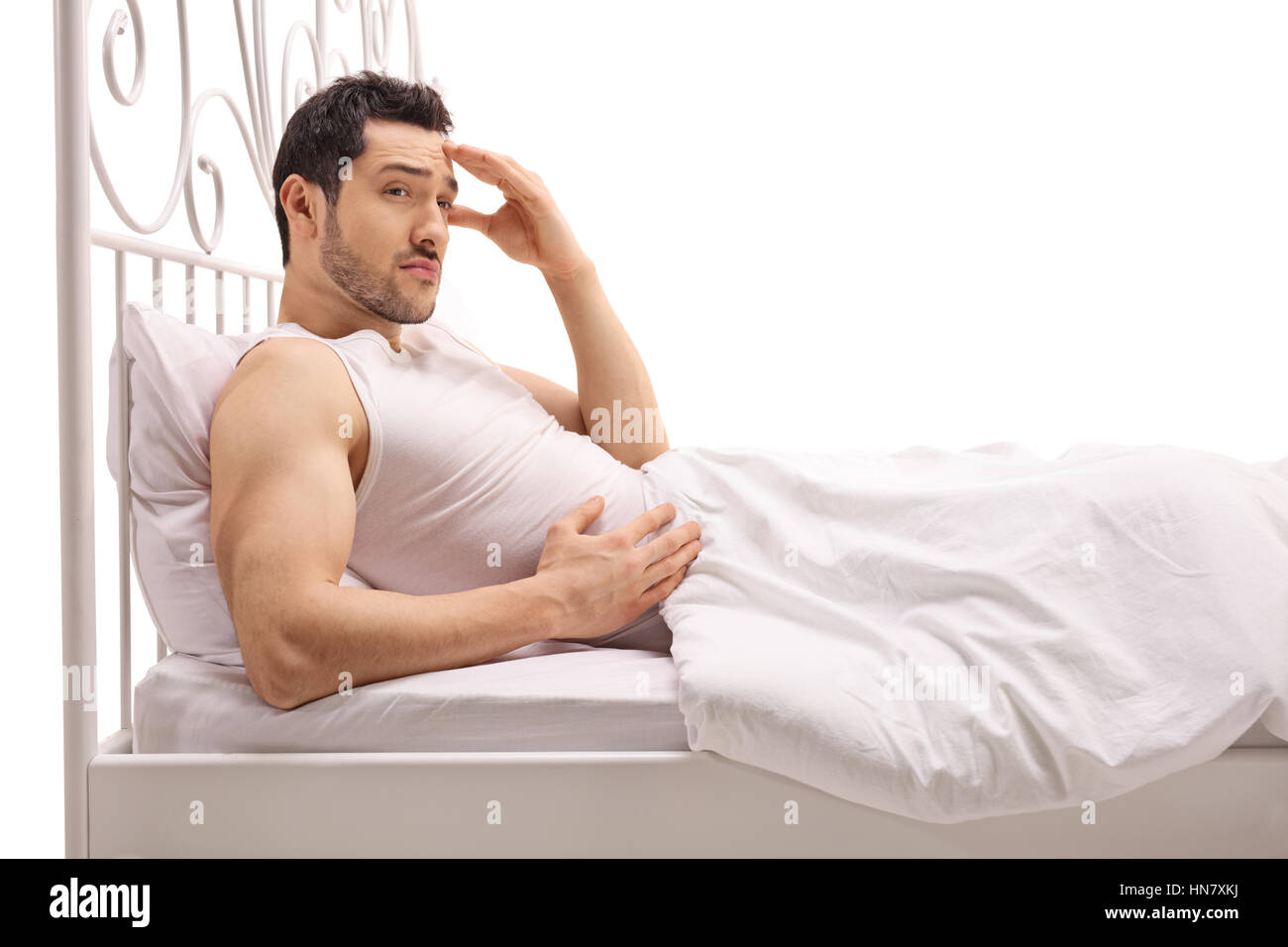 Worried guy lying in bed isolated on white background - Stock Image