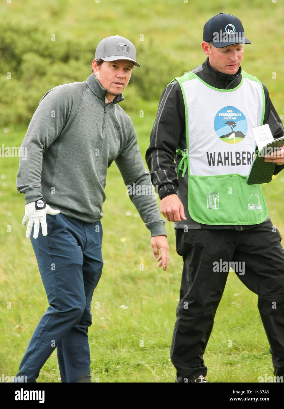 Pebble Beach, California, USA. 9th February, 2017.  Mark Wahlberg and caddy looking for his lost ball on the first - Stock Image