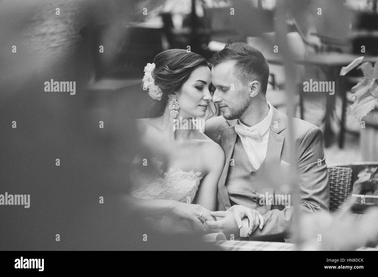 Happy couple kissing while sitting in street cafe. The bride and groom in a cafe, man hugging woman, couple looking - Stock Image