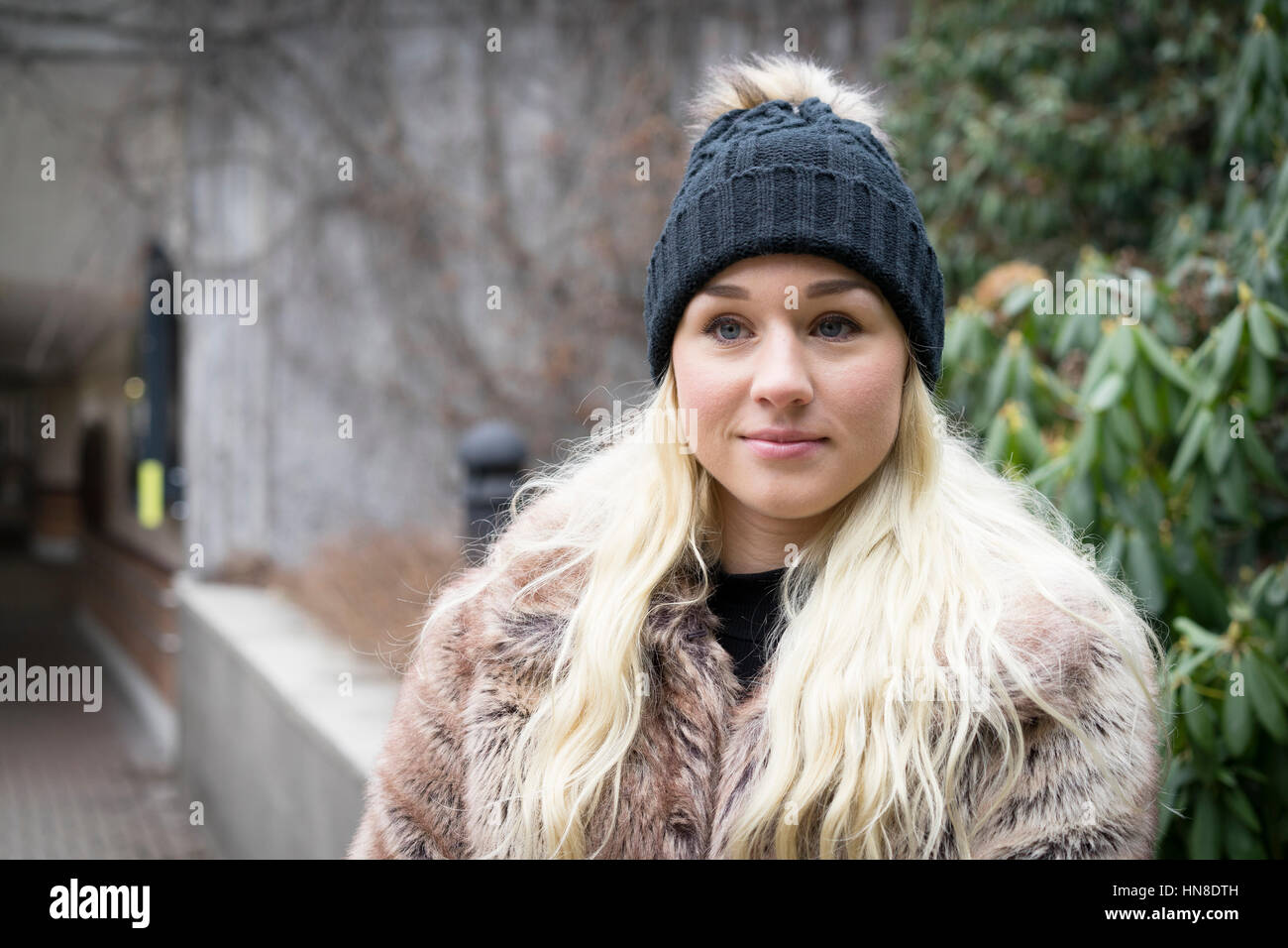 Beautiful blonde caucasian fashion woman in cap and a fur coat. Swedish Scandinavian ethnicity. Winter and outdoor - Stock Image