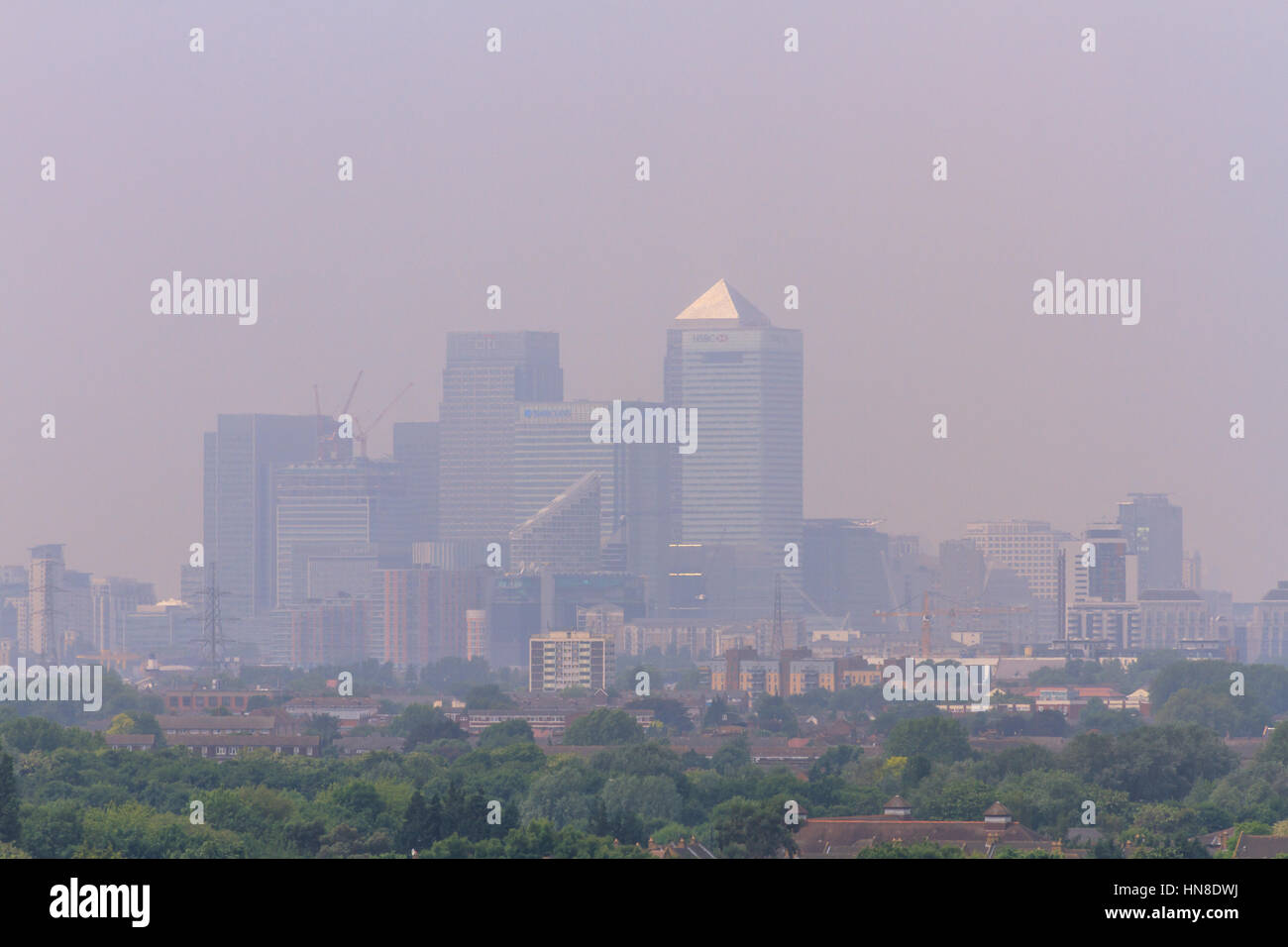 London skyline smog. Hazy day, smog, air pollution over Canary Wharf city of London, viewed from Becton in East - Stock Image