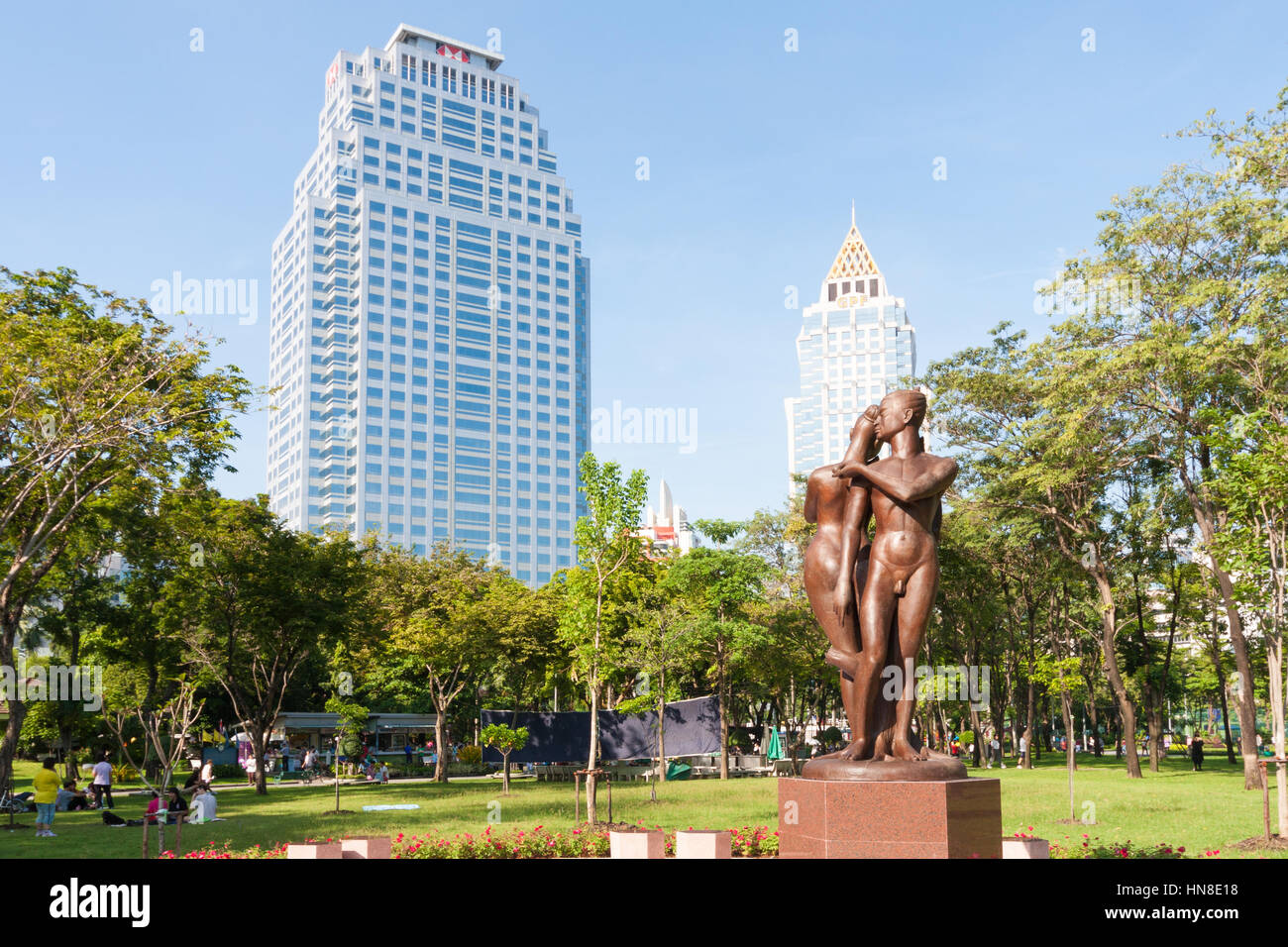 Statue and office buildings from Lumphini park, Bangkok, Thailand - Stock Image