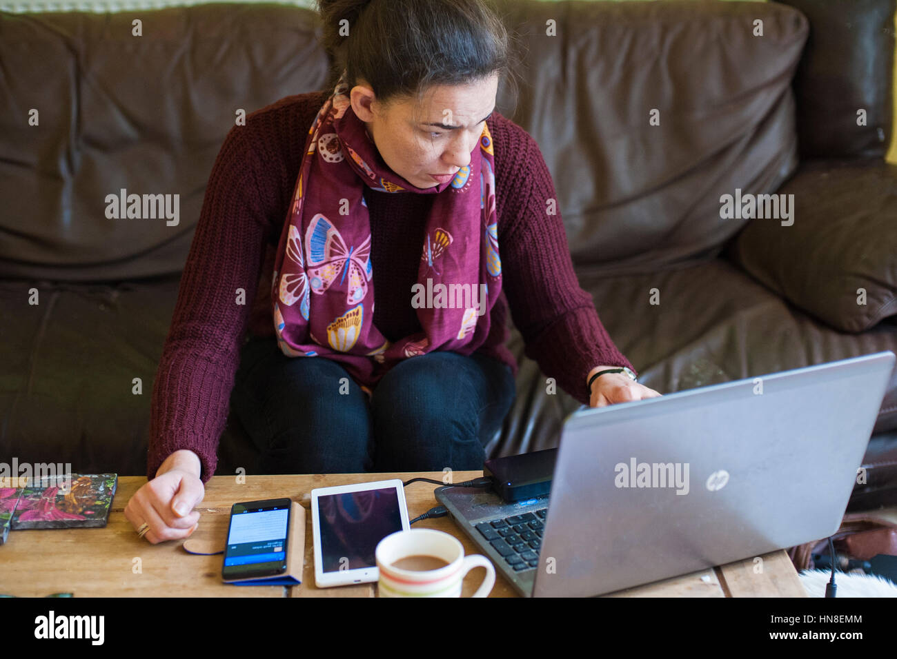 A woman in her thirties working from home with a laptop, mobile phone and tablet on coffee table - Stock Image