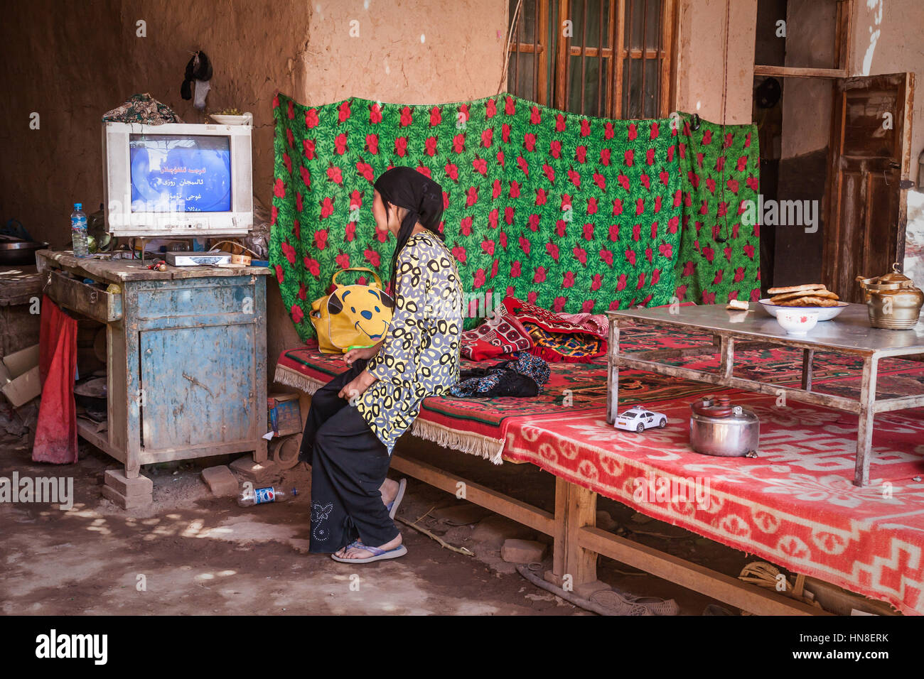 Young woman watching tv, inside Uighur house, Toyuq Village, Xinjiang, China. - Stock Image