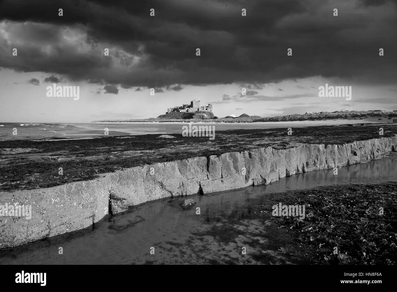 Rainbow and Storm, Bamburgh Castle, Bamburgh village, North Northumbrian Coast, Northumbria County, England, UK - Stock Image