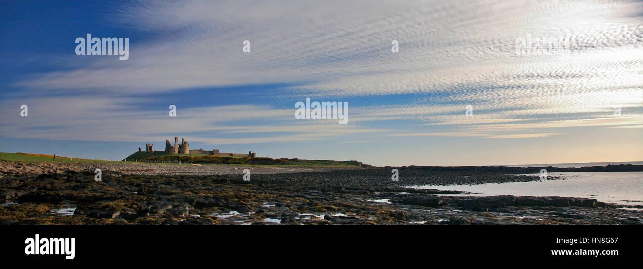 Summer blue skies, Dunstanburgh Castle, North Northumbrian Coast, Northumbria County, England, UK - Stock Image