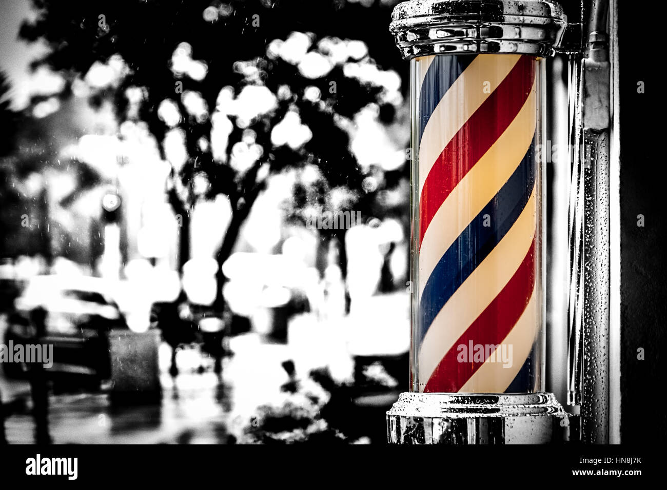Rain collecting on a barber shop pole in southern California. - Stock Image