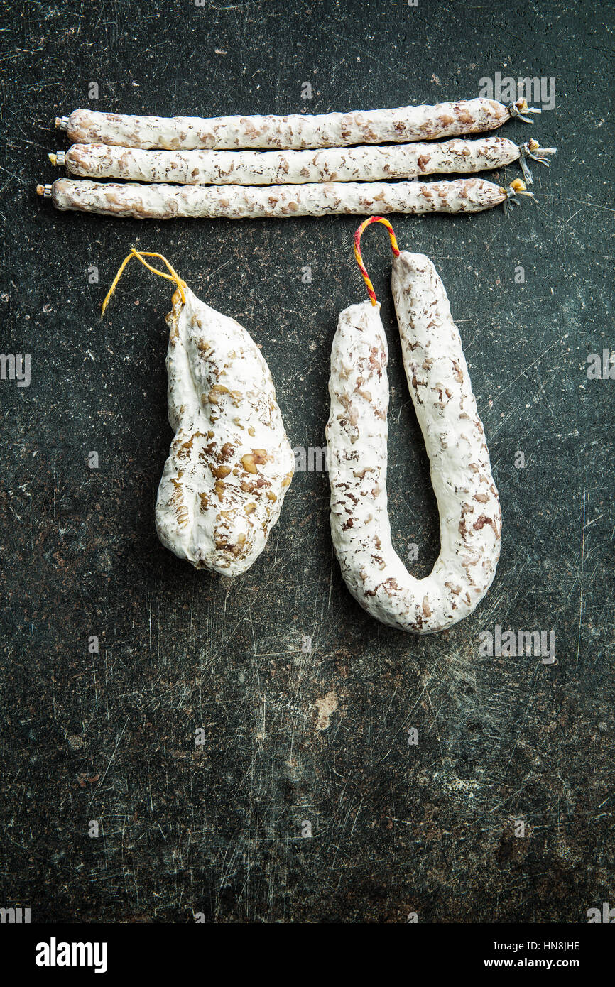 Tasty salami with white mold on kitchen table. - Stock Image