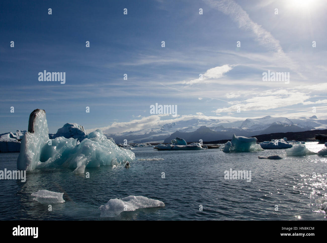 An iceberg that has just turned itself over shows it's turquoise blue underside on Jokulsarlon glacial lagoon - Stock Image