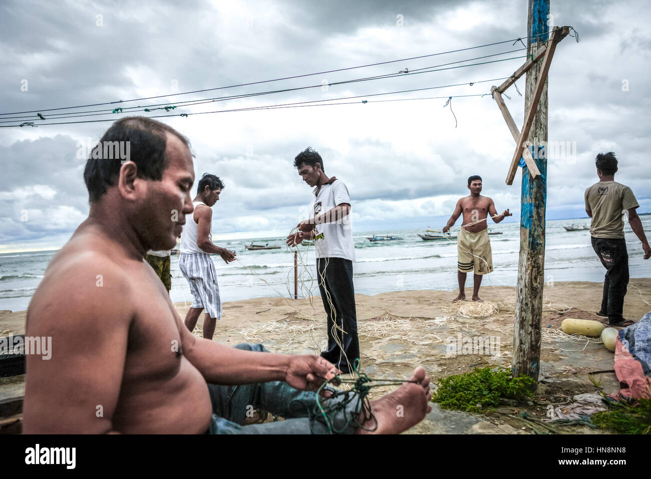 Fishermen repair fishing lines and fishnets on the beach as they wait for a good weather to sail. © Reynold - Stock Image