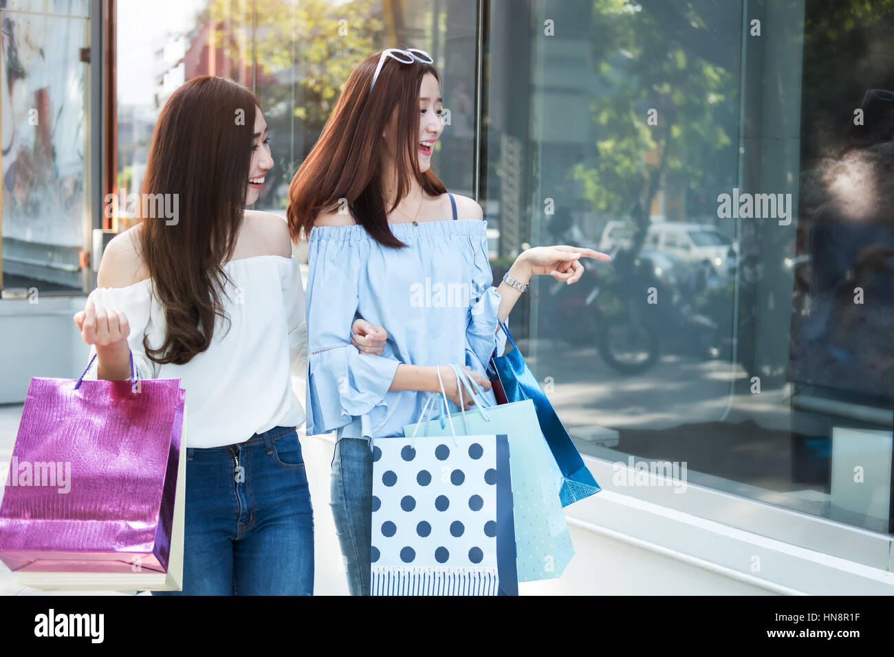 two young happy asian women shopping outdoor shopping mall in a holiday, vintage tone. - Stock Image